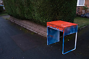 Table painted in red and blue paint left out in the street for recycling on 30th December 2020 in Birmingham, United Kingdom.