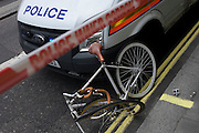 A mangled bicycle leans against a Metropolitan police van after a seemingly serious accident in the Strand.