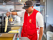 """26 JUNE 2020 - DES MOINES, IOWA: ENRIQUE HERNANDEZ makes deep fried foot long corn dogs in the American Grill trailer at Fair Food Friday in Des Moines. The 2020 Iowa State Fair, like many state fairs in the Midwest, has been cancelled this year because of the COVID-19 (Coronavirus) pandemic. The cancellation of the fair left many small vendors stranded with no income. Some of the fair food vendors in Iowa started """"Fair Food Fridays"""" on a property a few miles south of the State Fairgrounds. People drive up and don't leave their cars while vendors bring them the usual midway fare; corndogs, fried tenderloin sandwiches, turkey legs, deep fried Oreos, lemonaide and smoothies. Fair Food Friday has been very successful. The vendors serve 450-500 people per Friday and during the lunch rush people wait in line in their cars 30 - 45 minutes to place an order.      PHOTO BY JACK KURTZ"""
