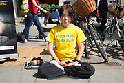 Members of Falun Gong or Falun Dafa sit in the lotus position meditating in protest in central London, UK. Their protest is concerning the alleged improsonment / torture and organ harvesting of fellow members in mainland China. They claim that tens of thousands of fellow practitioners are being held unlawfully in Chinese prisons. www.falundafa.org.tw