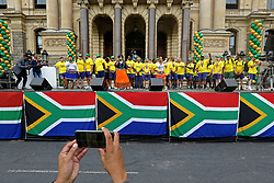 Monday 11th November 2019.<br /> City Hall, Grand Parade,<br /> And City Centre, Cape Town,<br /> Western Cape,<br /> South Africa.<br /> <br /> SPRINGBOKS CELEBRATE WINNING THE RUGBY WORLD CUP CHAMPIONSHIP IN 2019 WITH A COUNTRYWIDE VICTORY TOUR!<br /> <br /> SPRINGBOKS RUGBY WORLD CUP VICTORY TOUR CAPE TOWN!<br /> <br /> The Springboks take the stage outside the City Hall as they are cheered on by thousands of excited fans. South African Captain Siya Kolisi and his team mates enjoy the festivities prepared for them as a member of the media records the moment on his mobile smartphone.<br /> <br /> The reigning Rugby World Cup Champions namely the South African Springbok Rugby Team, celebrates winning the Webb Ellis Cup during the International Rugby Football Board Rugby World Cup Championship held in Japan in 2019 with their Victory Tour that culminated in the final city tour taking place in Cape Town. Thousands of South African fans filled the streets of the city all trying their best to show their support for their beloved Springboks and to celebrate them winning the Rugby World Cup for the third time. South Africa previously won the Rugby World Cup in 1995, 2007 and now again in 2019. South African Springbok Captan Siya Kolisi took the opportunity to speak to the gathered crowd about how something like this brings unity and that we should live together as a nation that practices what is known as ubuntu. Ubuntu is a quality that includes the essential human virtues of compassion and humanity. This image taken in Cape Town on Monday 11th November 2019.<br /> <br /> This image is the property of Seven Bang Media Group (Pty) Ltd, hereinafter referred to as SBM.<br /> <br /> Picture By: SBM / Mark Wessels. (11/11/2019).<br /> +27 (0)61 547 2729<br /> mark@sevenbang.com<br /> www.sevnbang.com<br /> <br /> Copyright © SBM. All Rights Reserved.