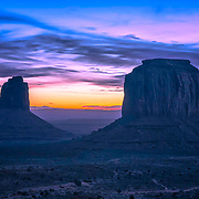 The East Mitten and Merrick Butte in silhouette as dawn breaks across Monument Valley.