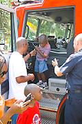 Black dad helps son age 3 from fire engine cab at firefighting demonstration. Aquatennial Beach Bash Minneapolis Minnesota USA