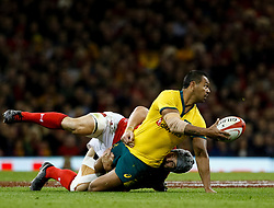 Kurtley Beale of Australia offloads despite the attentions of Jonathan Davies of Wales<br /> <br /> Photographer Simon King/Replay Images<br /> <br /> Under Armour Series - Wales v Australia - Saturday 10th November 2018 - Principality Stadium - Cardiff<br /> <br /> World Copyright © Replay Images . All rights reserved. info@replayimages.co.uk - http://replayimages.co.uk