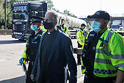 Insulate Britain climate activist Reverend Tim Hewes is arrested by Surrey Police after blocking the clockwise carriageway of the M25 between Junctions 9 and 10 as part of a campaign intended to push the UK government to make significant legislative change to start lowering emissions on 21st September 2021 in Ockham, United Kingdom. Both carriageways were briefly blocked before being cleared by Surrey Police. The activists are demanding that the government immediately promises both to fully fund and ensure the insulation of all social housing in Britain by 2025 and to produce within four months a legally binding national plan to fully fund and ensure the full low-energy and low-carbon whole-house retrofit, with no externalised costs, of all homes in Britain by 2030.
