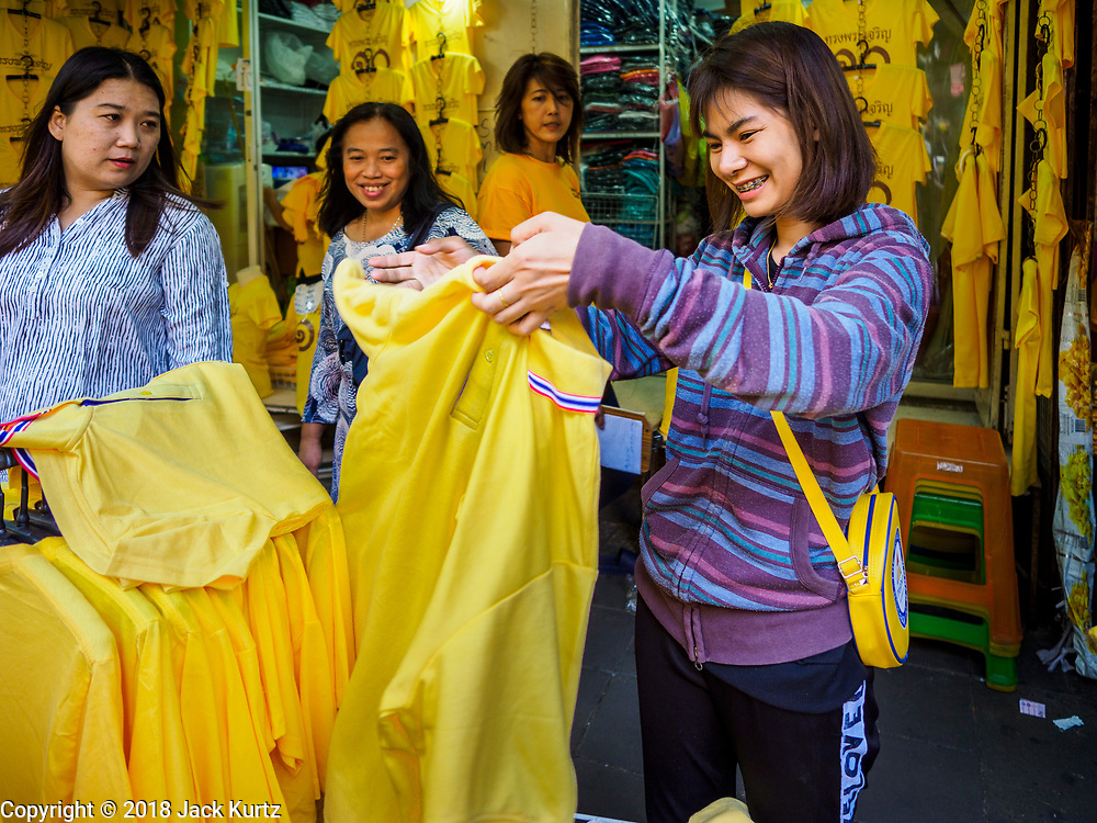 """03 JULY 2018 - BANGKOK, THAILAND: A girl looks at shirts that say """"Long Live the King"""" at a shop in Bobae Market. The birthday of King Maha Vajiralongkorn Bodindradebayavarangkun, Rama X, is 28 July. The King, the only son of Thailand's late King Bhumibol Adulyadej, became the King of Thailand in 2016 after the death of his father. King Vajiralongkorn was born on 28 July 1952, a Monday. In Thai culture each day of the week has a color, and yellow is the color is associated with Monday, so people wear yellow for the month before his birthday to honor His Majesty.    PHOTO BY JACK KURTZ"""