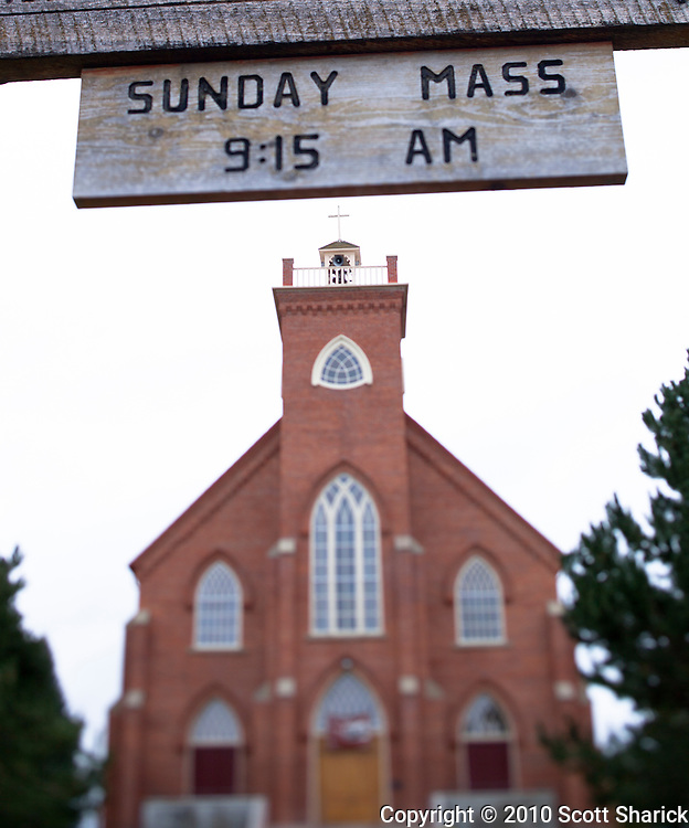 A sign announces the time of Sunday Mass at a red brick church. Taken with a shallow depth of field. Missoula Photographer, Missoula Photographers, Montana Pictures, Montana Photos, Photos of Montana