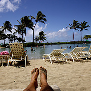 KAUAI, HI, July 13, 2007: Relaxing in the sun next to the saltwater lagoon at the Hyatt Regency Resort and Spa in Poipu on the island of Kauai.