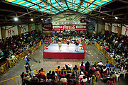 Wide view of wrestling ring with fighters in, and audience, in a sports hall. Lucha Libre wrestling origniated in Mexico, but is popular in other latin Amercian countries, including in La Paz / El Alto, Bolivia. Male and female fighters participate in the theatrical staged fights to an adoring crowd of locals and foreigners alike.
