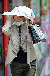 ©Licensed to London News Pictures 24/09/2020  <br /> Bromley, UK. A lady holds a bag over her head. Wet and windy weather today for shoppers in Bromley High Street, Bromley, South East London. The next two day are expected to bring thunder and gales to the UK. Photo credit:Grant Falvey/LNP