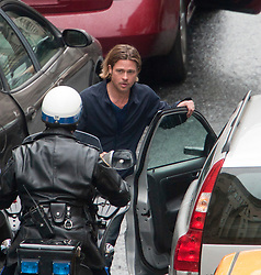 """Day two of filming. Brad Pitt watches the approaching police motorbike on the set of the movie """"World War Z"""" being shot in the city centre of Glasgow. The film, which is set in Philadelphia, is being shot in various parts of Glasgow, transforming it to shoot the post apocalyptic zombie film.."""
