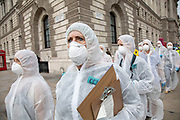 Extinction Rebellion 'crime scene investigators' in white suits and masks walk along Whitehall into Parliament Square to investigate areas of ecocide in a performance on 7th September 2020 in London, United Kingdom. The 20 investigators were protesting at the Brazilian government's alleged involvement in ecocide in the Amazon, and the UK government's ecocide along the HS2 route. Extinction Rebellion is a climate change group started in 2018 and has gained a huge following of people committed to peaceful protests. These protests are highlighting that the government is not doing enough to avoid catastrophic climate change and to demand the government take radical action to save the planet.
