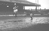 Football - 1966  1967 First Division - Manchester City 1 Manchester United 1<br /> <br /> Mike Doyle (City) jumps with Bill Foulkes as Nobby Stiles looks on, on a water logged, muddy pitch at Maine Road.<br /> <br /> 21/01/1967