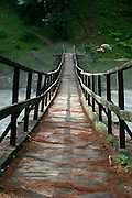 India, Kasol, Kullu District, Himachal Pradesh, Northern India A rope bridge over a river of gushing water