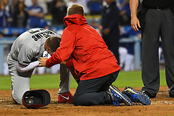 May 28, 2018 - Los Angeles, CA, U.S. - LOS ANGELES, CA - MAY 28: Philadelphia Phillies left fielder Rhys Hoskins (17) lays on the ground with a trainer after fouling a pitch off his face during a MLB game between the Philadelphia Phillies and the Los Angeles Dodgers on Memorial Day, May 28, 2018 at Dodger Stadium in Los Angeles, CA. (Photo by Brian Rothmuller/Icon Sportswire) (Credit Image: © Brian Rothmuller/Icon SMI via ZUMA Press)