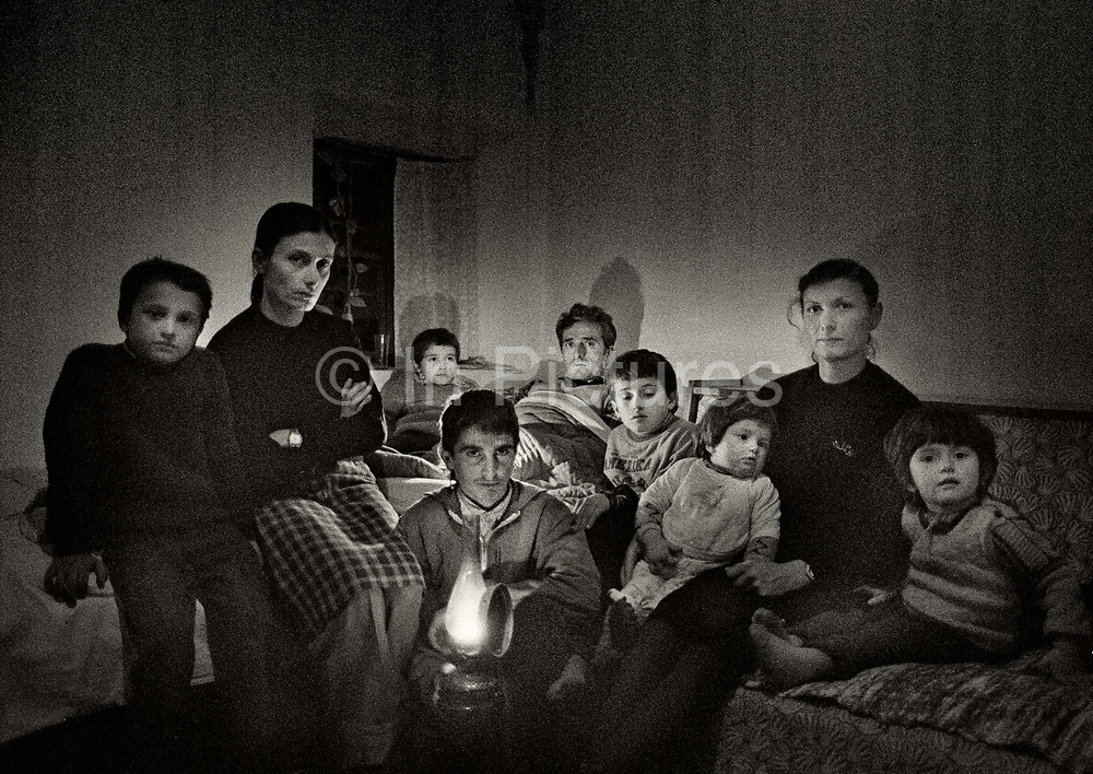 """The familly of Murat Balia who was killed ina blood feud with the familly of Amathj Mehmed. His nephew, Myftar Balia, is lying in the bed with the wounds from 8 bullets. He is surrounded by his familly and his son Edward (holding the lamp) aged 17 is bound by the Kanune (code of behavior going back hundreds of years) to defend his family's honour.<br /> <br /> The Kanun included an elaborate legal code trying to regulate blood feud (gjakmarrya) – a system of reciprocal """"honour killings"""". According to the Code, if a man is deeply affronted, his family has the right to kill the person who has insulted him. However, by doing this, the family will become a target for revenge on the part of the victim's family. The victim's closest male relative is obliged to kill the murderer of his family member. The pattern of reprisal killings thus formed has been passed on for generations of families and has been manifested up to the present day in Albania """"Blood is never lost"""", states the Kanun."""