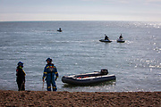 Watched by Border Force officers on Jet ski's the Coast Guard removes a dinghy from the sea that brought 13 Asylum seekers safely to the beach on the 8th of October 2021 in Folkestone, United Kingdom. The Home Office has begun using Jet Ski's or personal water crafts to move along the coast quicker and intercept small boats used by asylum seekers to cross the channel from France.