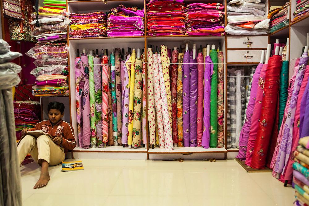 A boy studying in a fabric shop, Jodhpur, India.