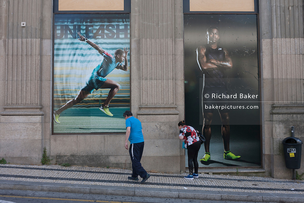 Two locals cough together beneath ad posters for sportswear outside a sports shop in Porto, Portugal.