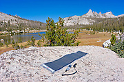 Solar panel charging a cell phone on a boulder, Echo Lake, Yosemite National Park, California