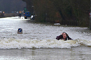 © Licensed to London News Pictures. 10/02/2014. Old Windsor, UK. A woman becomes couaght up in a lorries wash.  Flooding in OLD WINDSOR in Berkshire today 10th February 2014 after the River Thames burst its banks. The Environment Agency has issued 14 Severe Flood Warnings alone the Thames. Photo credit : Stephen Simpson/LNP