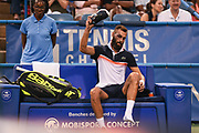 BENOIT PAIRE changes shoes at the Rock Creek Tennis Center.