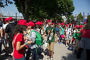 Group of young European student tourists wearing red caps walk along the South Bank in London, UK. The Southbank area has become a focal point in London for tourists and tourism with visitors flocking here in their thousands to experience art and culture.