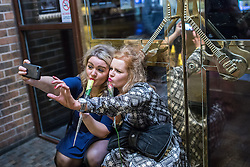 © Licensed to London News Pictures . 21/12/2013 . Manchester , UK . Two women pose for a selfie . Christmas revellers out in the rain in Manchester on Mad Friday , the last Friday night before Christmas which is typically one of the busiest nights of the year for police and ambulance crews . Photo credit : Joel Goodman/LNP