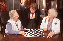 Two elderly women in residential home playing game of draughts with warden watching,