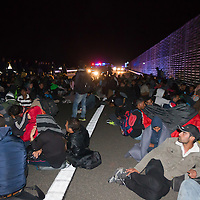 Illegal migrants take a rest as they walk with police escort on highway M5 after they broke out and run away from custody through a line of police officers near Roszke (about 174 km South of capital city Budapest), Hungary on September 07, 2015. ATTILA VOLGYI