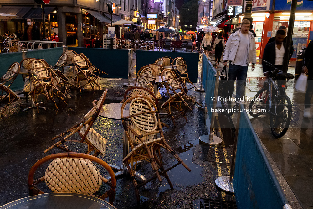 On a rainy night in Soho, tables set up on Old Compton Street for social distancing remain vacant at a time when recently re-opened bars and restaurants are desperate for customer business during the coronavirus pandemic, on 27th August 2020, in London, England.