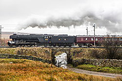 © Licensed to London News Pictures. 06/02/2016. Shap Wells UK. The iconic steam train the Flying Scotsman 60103, the first Locomotive to reach 100mph in 1934 has made it's first main line test run this morning hauling the Cumbrian Mountain Express from Carnforth to Carlise after a £4.2m restoration. Pictured travelling through Shap Wells approaching the Shap Summit at 914 ft/278m above sea level. Photo credit: Andrew McCaren/LNP