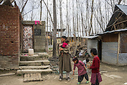 Shugufta, 29, tries to clean up her collapsed house as her husband carries their son Zainab, 10 months, while their other children Muzamil, 6, Azra, 5, and Igra, 8, play in front of their temporary shelter in Narbal village, Jammu and Kashmir, India, on 24th March 2015. When the floods hit in the middle of the night, Shugufta and her family had to walk 5 miles to find shelter. Save the Children supported the family with shelter kits, blankets, hygiene items, food and tarpaulin, which they have used to build a temporary shelter next to their crumbled home. Photo by Suzanne Lee for Save the Children