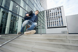 Happy teenage jumping over banister holding laptop after work, Bavaria, Germany