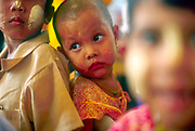 Child at nersery school. Rangoon, Burma 2000. Face covered with Thanaka, a yellowish cosmetic paste made from ground bark which is commonly applied to the face in Burma.