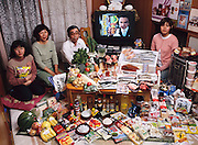 (MODEL RELEASED IMAGE).The Ukita family: Sayo Ukita, 51, and her husband, Kazuo Ukita, 53, with children Maya, 14 (holding chips) and Mio, 17; in their dining room in Kodaira City, Japan, with one week's worth of food. The Ukita family is one of the thirty families featured in the book Hungry Planet: What the World Eats (p. 180).