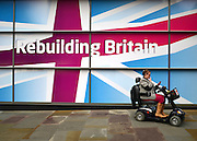 © Licensed to London News Pictures. 01/10/2012. Manchester, UK A woman on a mobility scooter waits in front of a poster with labour's message 'Rebuilding Britain'. Labour Party Conference Day 2 at Manchester Central. Photo credit : Stephen Simpson/LNP