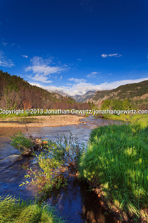 Majestic mountains overlook a stream flowing through a tranquil meadow in Rocky Mountain National Park near Estes Park, Colorado.