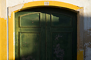 Light and shade on typical white and yellow house with green front door in Evora, Portugal