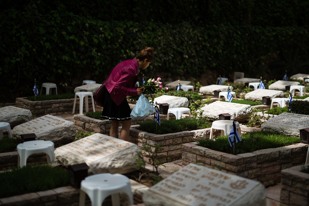 An Israeli woman places flowers on graves of fallen Israeli soldiers, at the Mount Herzl military cemetery in Jerusalem, on April 20, 2015, ahead of the annual Memorial Day honoring fallen soldiers and Victims of Terror, which begins Tuesday night.