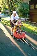 Grandpa age 60 pushing granddaughters ages 4 and 2 in toy car.  Downers Grove Illinois USA