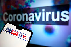 The EFL Sky Bet logo seen displayed on a mobile phone with an illustrative model of the Coronavirus displayed on a monitor in the background. Photo credit should read: James Warwick/EMPICS Entertainment