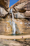 Hike Lower Calf Creek Falls trail 6 miles round trip (600 feet gain), in Grand Staircase-Escalante National Monument, Utah, USA. The beautiful cascade drops 126 feet (38 meters) from sandstone cliffs stained with fascinating patterns of desert varnish. Directions: From the town of Escalante, drive 15 miles east on Scenic Byway 12 to Calf Creek Recreation Area day-use parking and campground. More about desert varnish: Manganese-rich desert varnish requires thousands of years to coat a rock face that is protected from precipitation and wind erosion. The varnish likely originates from airborne dust and external surface runoff, including: clay minerals, oxides and hydroxides of manganese (Mn) and/or iron (Fe), sand grains, trace elements, and usually organic matter. Streaks of black varnish often occur where water cascades over cliffs, but wind doesn't sculpt its shape. Varnish color varies from shades of brown to black. Manganese-poor, iron-rich varnishes are red to orange, and intermediate concentrations are shaded brown. Manganese-oxidizing microbes may explain the unusually high concentration of manganese in black desert varnish, which can be smooth and shiny where densest.