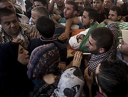 July 26, 2018 - Gaza, Gaza Strip, Palestine - (EDITORS NOTE: Image depicts death.).Mourners carry the body of Palestinian Hamas militant Mohammad Al-Areer who was killed in Israeli tank fire, during his funeral in Gaza City..The military wing of Gaza's rulers Hamas have vowed revenge after Israeli strikes late July 25 killed three members of the group in the latest flare-up of violence. Israel said the artillery fire late Wednesday was in retaliation for shots fired at troops along the border which injured one soldier. (Credit Image: © Mahmoud Issa/SOPA Images via ZUMA Wire)