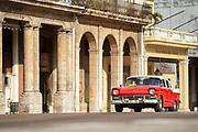 Vintage car on street between buildings, Paseo de Marti, Havana, Cuba