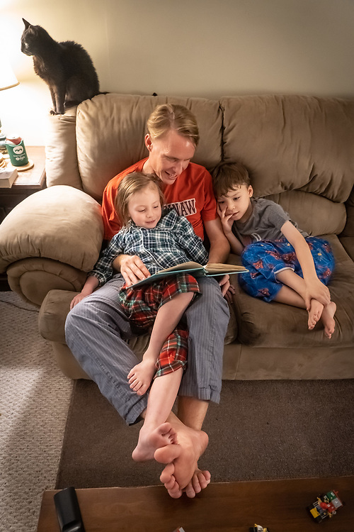 Michael reads a bedtime story to Sam and Eleanor as Loki the cat stands by atop the sofa.
