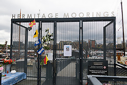© Licensed to London News Pictures. 18/06/2016. LONDON, UK.  Flowers and flags at the entrance of Hermitage Moorings on the River Thames in Wapping, where the MP lived on a houseboat. The Labour MP for Batley and Spen was about to hold her weekly constituency surgery in Birstall Library on16 June 2016 when she was shot and stabbed in the street and later died. Friends and neighbours from the local community continue to visit Hermitage Moorings this morning to pay tribute to Jo Cox.  Photo credit: Vickie Flores/LNP