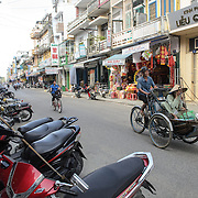 A man rides a rickshaw on a street in Hue, Vietnam.