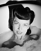 0003-004. Enjoying a bubble bath in a cast iron porcelean bathtub. Marian Fresk (wife of photographer) Ca, 1942.