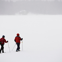 A couple snowshoeing in a storm on Swanzey Lake, New Hampshire.
